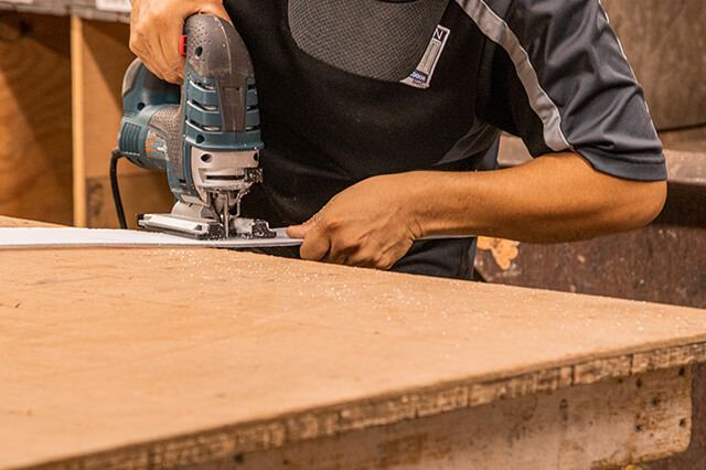 Employee cutting materials for door in Milwaukee store and showroom